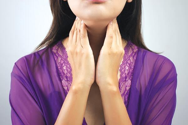 Nainen tunnustelee kaulalla sijaitsevaa kilpirauhastaan.
