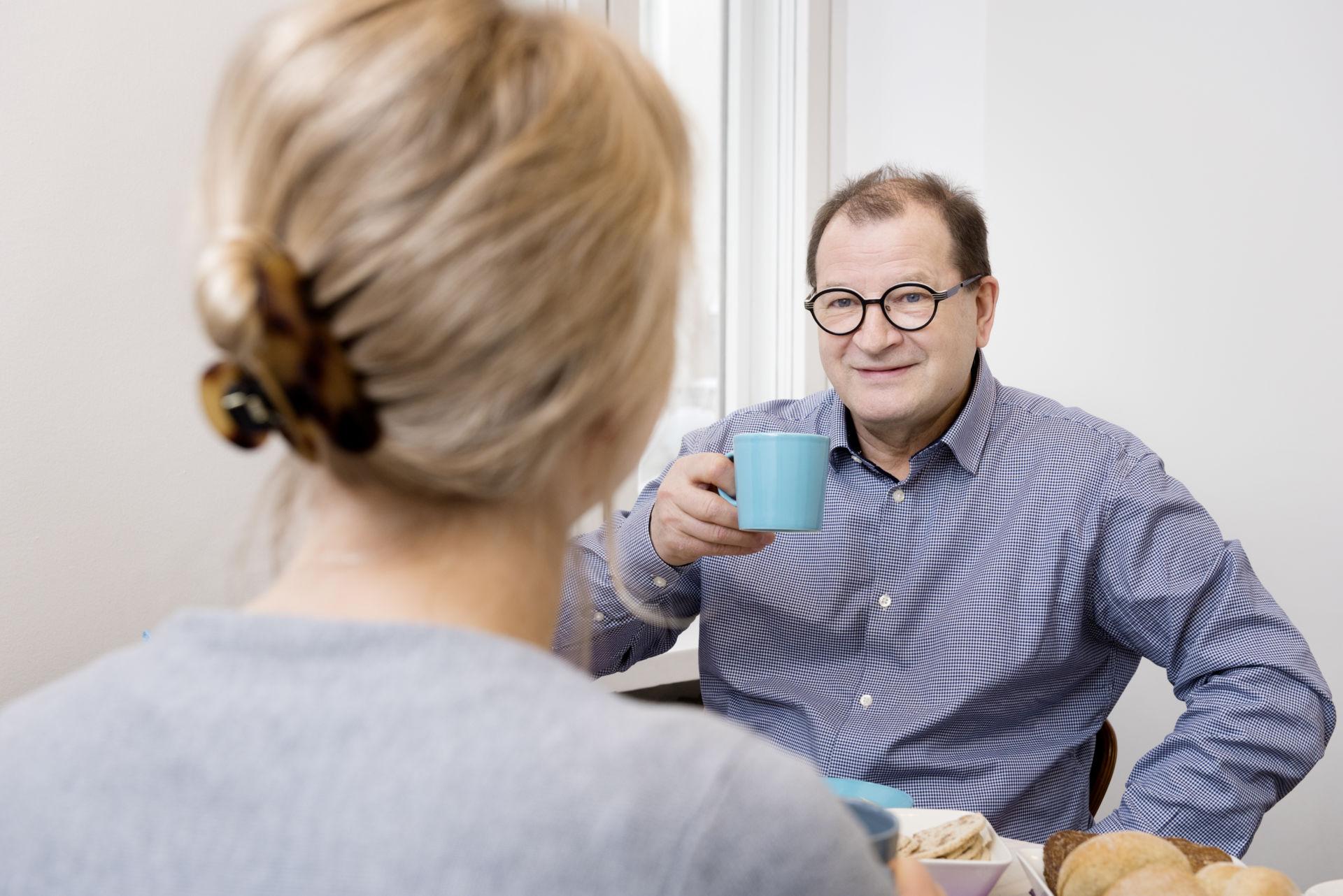 Mies nauttii kahvia ja hymyilee katsoessaan naista. Miehen kasvot ovat kohti kameraa, naisesta näkyy selvä.