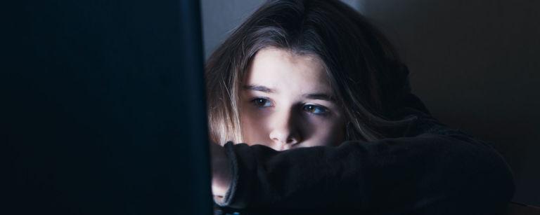 Mitä suojaikäraja tarkoittaa? Kuvassa tyttö istuu pimeässä ja katsoo kirkasta ruutua
