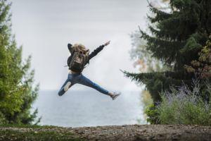 Hyppäävä tyttö metsätiellä. TIen varrella kuusia.