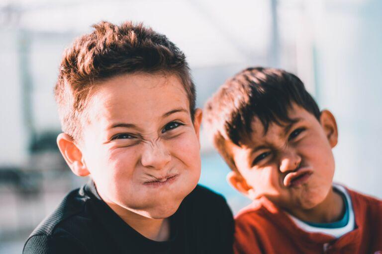 På bilden två pojkar som gör grimaser