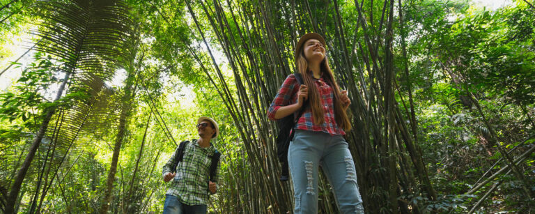 Two young smiling persons walking in a bamboo-forest