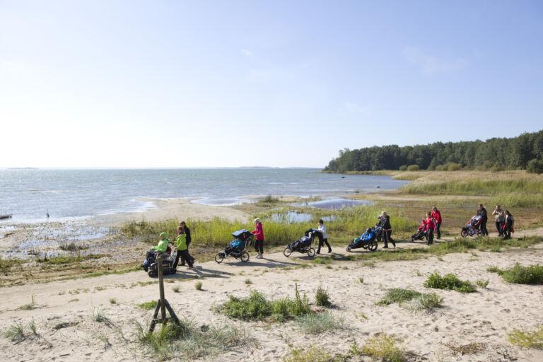 Ihmisiä kulkee hiekka rannalla peräkkäin. Osa heistä istuu maastovälineessä ja osa työntää heitä. On kesä, aurinko paistaa ja taustalla näkyy meri sekä rannan ruohikkoa.