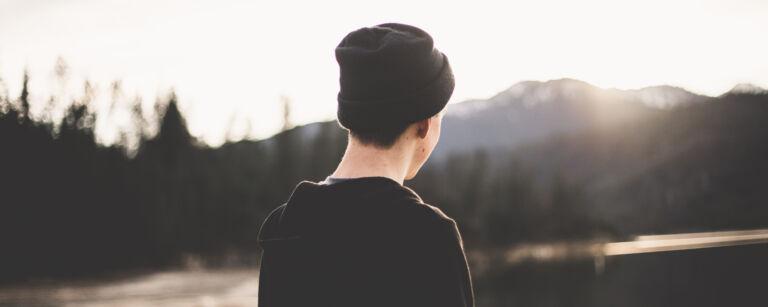 På bilden en pojke med svart luva som betraktar ett landskap med en älv och ett berg. Solen skiner på hans ansikte.