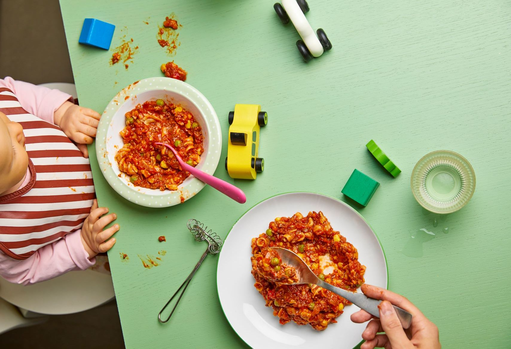 Ruokapöytä, jossa lapsen ja aikuisen italianpatalautanen ja leluja