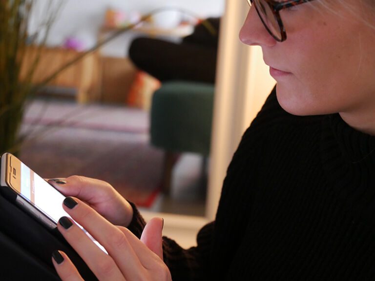 Nainen käyttää kännykkää.