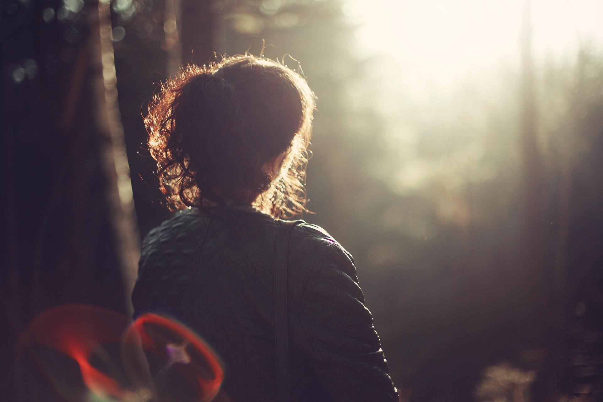 Nainen istuu selkä kohti kameraa ja tuijottaa kohti valoa.