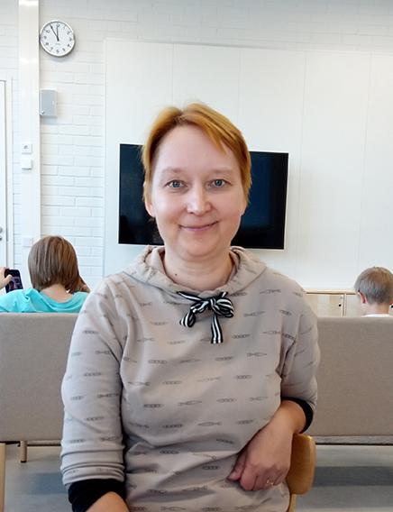 Mindfullness-ohjaaja Heli Mäkelä istuu luokassa.