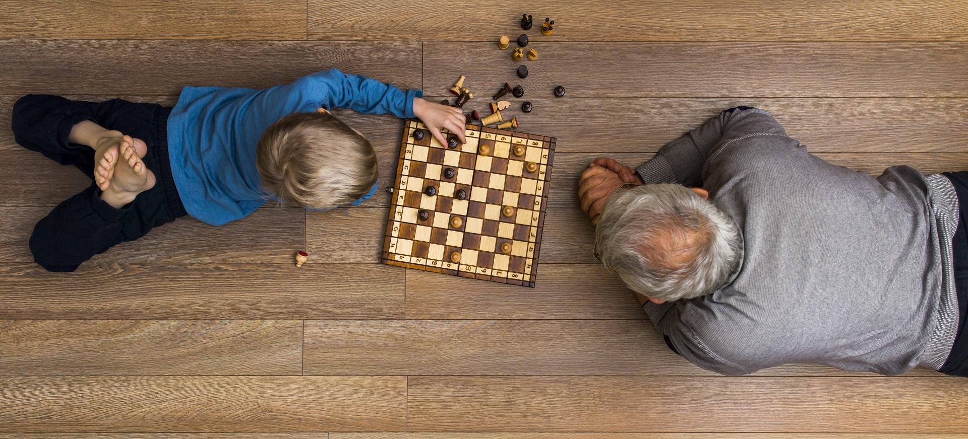 Isoisä ja poika lattialla pelaamassa shakkia