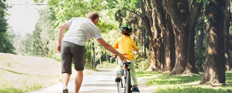 lapsi pyöräilee, mies tukee kädellään lasta
