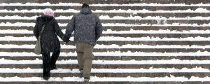 Kuvassa kaksi hahmoa nousemassa lumisia portaita käsi kädessä.