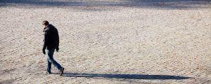Kuvassa kadulla kävelevä mies ja miehen varjokuva.