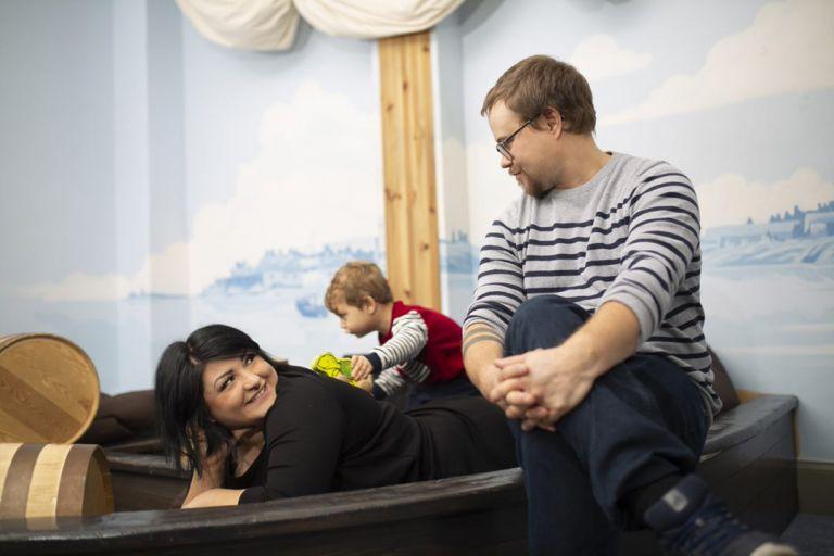 Isä ja äiti katsovat toisiaan hymyillen, taaperoikäinen lapsi leikkii taustalla