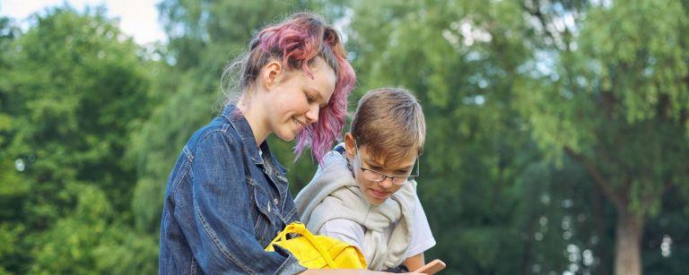 Kaksi nuorta istuu vierekkäin puistossa. Hymyilevät vienosti ja katsovat yhdessä toisen nuoren puhelimen näyttöä.
