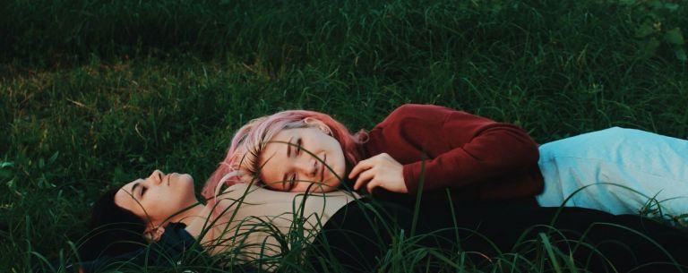 Kuvassa makaa kaksi henkilöä nurmikolla. Toisen pää on toisen sylissä, ja hän hymyilee.