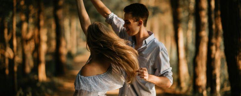 Naisoletettu henkilö ja miesoletettu henkilö tanssivat paritanssia ulkona. Takana auringon valaisemia puita.