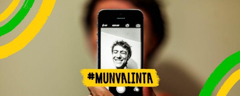 Poikaoletettu henkilö ottaa selfien itsestään. Puhelimen näytöltä näkyy hänen kuvansa. Hän hymyilee. Kuva on muokattu Mun valinta -kampanjan kehyksillä, ja keskellä alareunassa on Mun valinta -kampanjan logo.